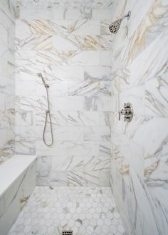 The marble walk-in shower is shot through with veins of gray and gold.