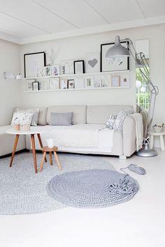 salón en tonos neutros y gris- estanterias con cuadros balncos