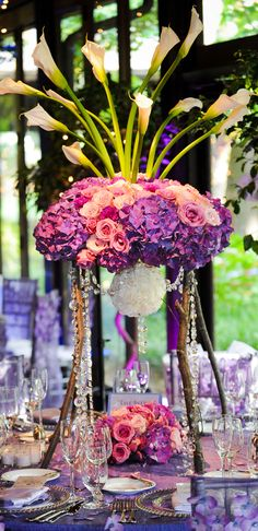 Stunning tall centerpieces of purple hydrangeas, lavender and pink roses, and white calla lilies accented with strands of crystals.