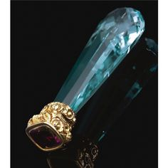 AQUAMARINE AND AMETHYST DESK SEAL, CIRCA 1830. The tapered faceted aquamarine handle, to a gold work mount of shell, foliate and scroll motifs, terminating on a collet -set cushion-shaped amethyst.