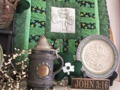 Small green shamrock print quilt with a green stitchery center hanging on a harp...green beer stein & Irish Blessing plate make up this display.