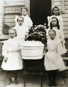 Funeral of a little girl. Her girl friends are the pallbearers. Casket resting on table and covered with flowers.The photo was taken in Newberry, Michigan around 1900.
