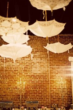 love the upside down umbrellas as decorations ~ can't help but love the brick wall and wall chandeliers ~ love it