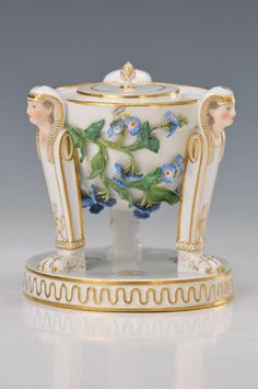 Inktpot, Meissen around 1880, Egyptian style,with Sphinx heads on three claw feet standing,opulent appliques of Forget-me-not flowers, onthis slightly damaged, polychrome painting, scattered flowers, gold decoration, round pedestal with meandering