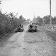 A Universal Carrier carrier passes a burnt-out German SdKfz 250/9 reconnaissance half-track near Troarn during Operation 'Goodwood', 19 July 1944