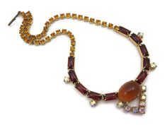 A lovely vintage topaz rhinestones necklace with amber tone and AB finish stones in gold tone metal.  No marks. Measures about 14.5 at the longest, but can be worn shorter depending on where you hook it. Some wear to the finish, and darkening to some of the stones.           I am always happy to answer any questions or send more photos when needed.   Thanks for shopping Vintage In Bloom  www.facebook.com/vintageinbloom    More pendants & necklaces: http://www.etsy.com/...