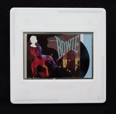 """David Bowie, a music legend, features on a set of Royal Mail special stamps issued in 2017. This £1.52 stamp design shows the 1983 'Lets Dance' album cover. The unused stamp is encased in a vintage slide mount, with glass, making this a unique piece of jewellery. A light blue paper is used to highlight the vinyl breakout detail. It is square in format and dimensions are approximately 2"""" x 2"""" - 50mm x 50mm."""