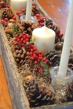 Rustic Christmas centerpiece with pine cones, berries, and candles..