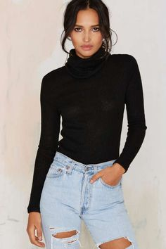 The No Chill Sweater is made in a black ribbed knit and features an oversized turtleneck, long sleeves, and stretch in fabric.