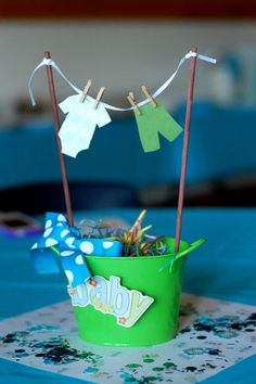 Centerpiece for baby shower tables. Paper cut-out clothes hung on ribbon with mini clothespins, poles stuck in play dough and covered in Easter grass. Dollar store tin bucket. pretty easy to make.