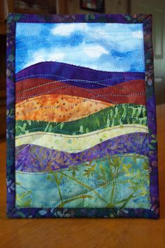 Landscape batik art quilt mounted on an easel-type picture frame for easy display. It attaches to the frame with a piece of Velcro on the back and it is detachable from the frame (easel frame included). This piece is made with batik cotton fabrics with raw-edge top stitching of layers together and quilted with decorative threads and measures 5 1/4 x 7 1/4 (also looks great matted and framed). The colors in this piece are rich purple/blue, brick red, orange, greens, and blue/green. **Looks…