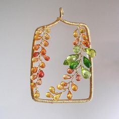 ......golden vines with shots of green..... This listing does not include chain. Please message me if you would like a chain. Made to order with a two week turnaround. Because it is handmade it wont be exact, but very close. 18 gauge 14k gold filled wire lengths have been hammered and forged into a rectangular pendant. Adored with gold, tangerine, and melon sapphire vines. Bright green peridot and grassy green chrome diopside sit on one side lending a bit of detail and dimension. Finished…