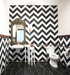 Contemporary powder room features walls clad in black and white chevron tiles lined with a green and gold pagoda mirror over a wall-mount sink next to tall round white nesting tables atop a black marble tiled floor.