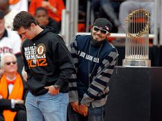 Sergio Romo hides behind Buster Posey as they take the podium to speak to the crowd during the World Series Civic Celebration after the World Series Victory Parade for the San Francisco Giants at the San Francisco Civic Center in downtown San Francisco, Calif., on Wednesday, Oct. 31, 2012. (LiPo Ching/Staff)