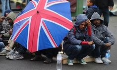 Eritrean migrants take cover from the rain under an umbrella during the daily food distribution at the harbour in Calais, northern France, May 27, 2014.