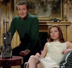 "'The £50,000 Breakfast', Series 5 ~ John Steed wears a dark green polo shirt  black trousers.  Emma sports a cream window pane check mini shift dress.  Sleeveless, with banded 3"" tan trim at the hem, which matches the tan high-collared and belted short length jacket. the dress is later worn with (right)."