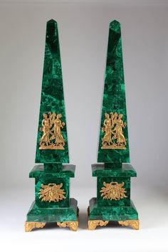 A pair of Malachite Marble Obelisks with Applied Ormolu Decorative Elements in the Neoclassical Style : Some Maidens with Flowers on the Obelisks, The Sun on the Pedestals ; the whole raised on decorative gilded feet. H. 29in - XXth Cent.