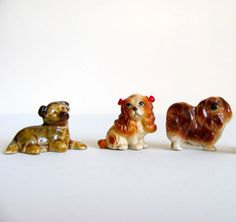 SOLD Vintage collection of three miniature ceramic dog figurines from various eras. Includes one German shepherd made by Wade, a Cavalier King Charles with red bows made in Japan, and a Pekingese made in Japan.