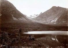 FAKf-100244.160199 Postkort med tekst: «Nøvedalstindane fra Standalseidet.». (JSR-Kode: A8-A-Natur). Bildet er teke i frå vestsida av Standalsvatnet i Hjørundfjorden. Motivet er teke omtrent i nedkant av der Standalshytta ligg i dag... og der det er laga til ei lita badestrand. (Informant: Eli Anne Tvergrov.) Landskap, vatn, Ørsta, Standalsvatnet