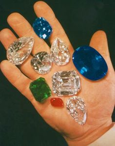 Harry Winston holds some of his Famous Gems in the palm of his hand. The 125.35ct Emerald cut Jonker Diamond is center. Just under the Jonker is the 94.80ct Pear shaped Star of the East Diamond. The 45.52ct Blue Hope Diamond rests between his index and middle finger. The 337.10ct Sapphire of Catherine the Great is next to his thumb, and the 70.21ct Idol's Eye Diamond is just above the Jonker. A matched pair of Pear shaped Diamonds and a larger Ruby are also shown