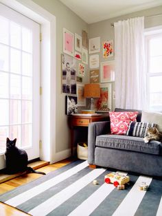 Turn a lonely corner into a cozy, friendly reading nook when you create a wrapping gallery wall. Try hanging family photos and art in various sizes for an eclectic, lived-in look. See more at A Lovely Lark »  - GoodHousekeeping.com