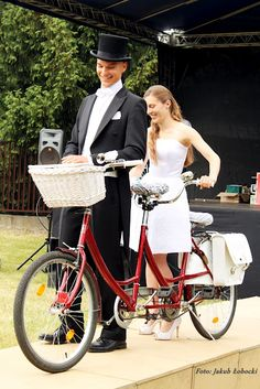 Formally dressed wedding couple on a red tandem with a white basket. A bicycle built for two.