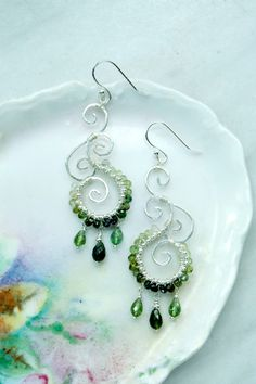 Hand formed sterling silver swirls wire wrapped together and edged with ombre green tourmaline beads and silver plated metal seed beads. Finished