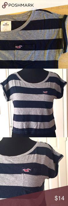 "SALE! Hollister Navy/Grey Striped Cropped Tee SALE! Hollister Navy Blue & Grey Striped Cropped Tee Shirt with Folded Sleeves. Measurements: Shoulders 24"", Chest 20"", Front Rise Length 15"" & Back Rise Length 18"".                                         ***Original List Price $17***                                           No Lowball Offers, Please! Hollister Tops Tees - Short Sleeve"