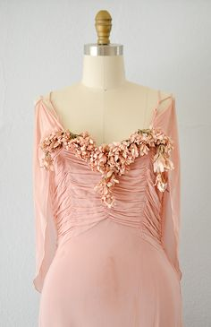 1930s romantic rose pink gown has gathered bodice with sweetheart neckline decked with clusters of pink blossoms. The thin double straps can be worn elegantly off the shoulder and the attached cape drapes with subtle drama. Bias cut dress has beautiful movement.