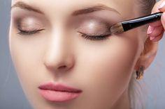 beautiful woman applying brown eye shadow using makeup brush makeup