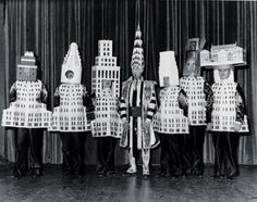 Architects dressed as their famous buildings at the 1931 Beaux-Arts Architect Ball. From left to right: Stewart Walker (Fuller Building), Leonard Schultze (Waldorf-Astoria), Ely Jacques Kahn (Squibb Building), William Van Alen (Chrysler Building), Ralph Walker (1 Wall Street), D.E.Ward (Metropolitan Tower), and Joseph H. Freelander (Museum of New York).