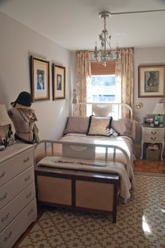 Small bedroom layout, art over the bed and curtains behind the bed. plus the lamp on the left side.