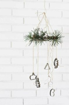 Easy diy chime made of a few pine twigs attached onto a metal ring and old  cookie cutters tied with twine.