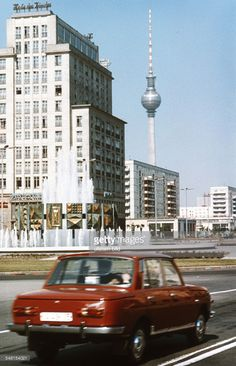 German Democratic Republic Bezirk Berlin (Ost-Berlin) East Berlin - red Wartburg car at the square Strausberger Platz in front of the building Haus des Kindes (house of the child) and the television tower