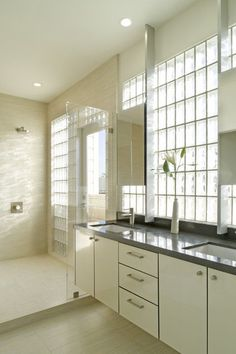 Love the metal bars holding the mirrors, while still allowing for windows behind.    modern bathroom by John Lum Architecture, Inc. AIA