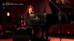 Carmen Paris muy concentrada al piano, al fondo podemos ver a parte del público disfrutando de la actuación