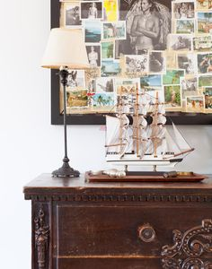 A collage of photos above a large antique chest of drawers.