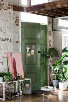Inviting loft/industrial style entry with vibrant green doors.