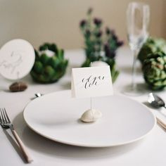 Wrap a thin wire around a river rock and attach an elegant paper card to it & use it as a place card