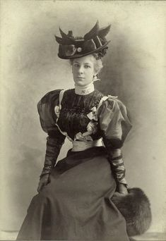 Woman with blonde hair dressed to the height of fashion in 1890 with muttonchop sleeves, tight laced corset, high neck collar, fur muff, and a hat decorated with bird wings