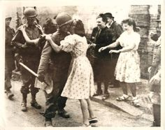 1944- American troops entering Paris get kissed by French girls, joyful over their liberation from Nazi rule.