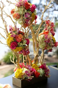Love this arrangement with bright flowers and gold branches