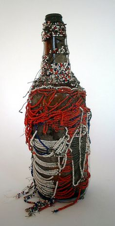 "Vodou Bottle (#VYB17)  Unknown artist, Haiti  Beads on fabric on glass bottle (+/- 3 1/2"" x 12""),  mid-20th century"