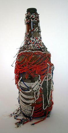 "Vodou Bottle (#VYB17)  Unknown artist, Haiti  Beads on fabric on glass bottle (+/- 3 1/2"" x 12""),  mid-20th century"