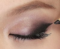 First, apply a shimmery mauve color (try MAC Pigment in Kitschmas) over the entire eyelid. Darken the outer eyelid with a dark plum color like MAC Eye Kohl in Prunella and wing it past your eye for the perfect 60s look. Draw a thin line along your upper lashes with a black liquid eyeliner. Line 1/4 of the outer corner of your lower eye with the plum color and highlight the inner corner with the mauve shade. Finish with a pair of falsies on top and black mascara on lower lashes.