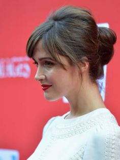 Beautiful! Long, parted bangs with a low, knotted bun and a pouf on top, plus a red lip