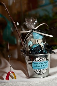Our wedding favors- white chocolate fish inside a mini pail, a fishing pole made out of a tree branch, and a mini hook attached with a gummy worm. My husband loves to fish so I had to incorporate his loves as well. We also got married right on the river. - Ashley Maxwell Photography