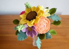 Whether for Mothers Day, a wedding, a special gift, or just because, this felt floral bouquet will brighten anyones day! No need for watering, these felt flowers will bloom forever.  :: Size ::  Approximately 7 diameter, 8 high Comprised of 7 flower stems & 8 greenery stems  :: Features ::  Ranunculus :: guava colored felt Sunflower :: lemonade colored felt Dahlias :: magenta, thistle colored felt Wildflowers :: butter, foxglove, lilac, mustard colored felt Greenery :: pistachio, spruce, ...