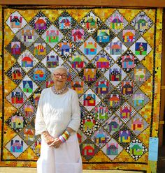 "Freddy Moran of Orinda CA in front of her quilt ""Houses on Point"" (80″ square). 2015 Sisters Outdoor Quilt Show. Photo by First Light Designs."
