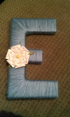 Wooden letter wrapped in yarn and flower attached. Easy and cheap gift idea!
